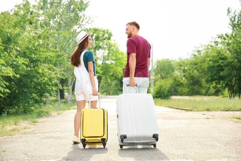 Schöne junge Paare mit den Koffern, die draußen gehen stockbilder