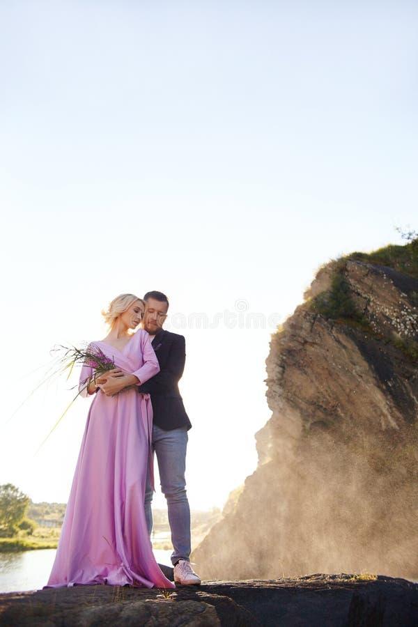 Schöne junge Paarumarmungen und -blicke weg und auf einander ein romantisches Datum am Fluss genießend Mann- und Frauenstellung stockfoto
