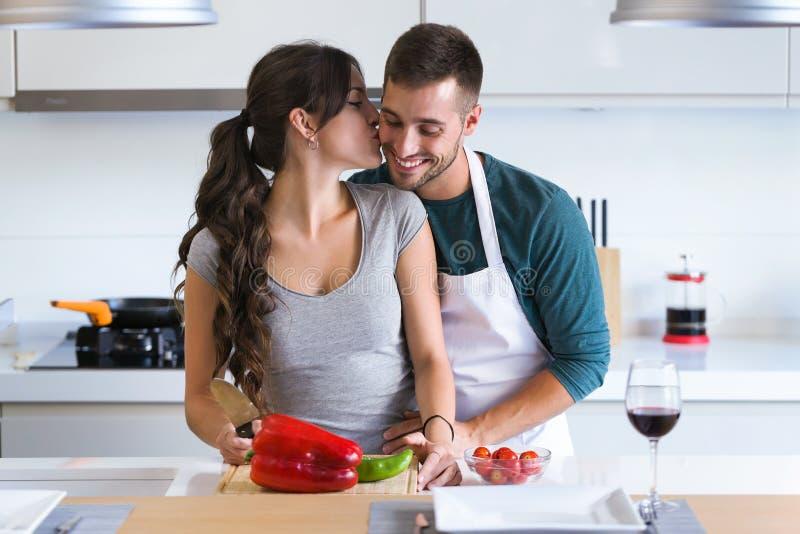 Schöne junge romantische Momente habende, umarmende und beim Gemüse zu Hause schneiden in der Küche küssende Paare stockfotografie