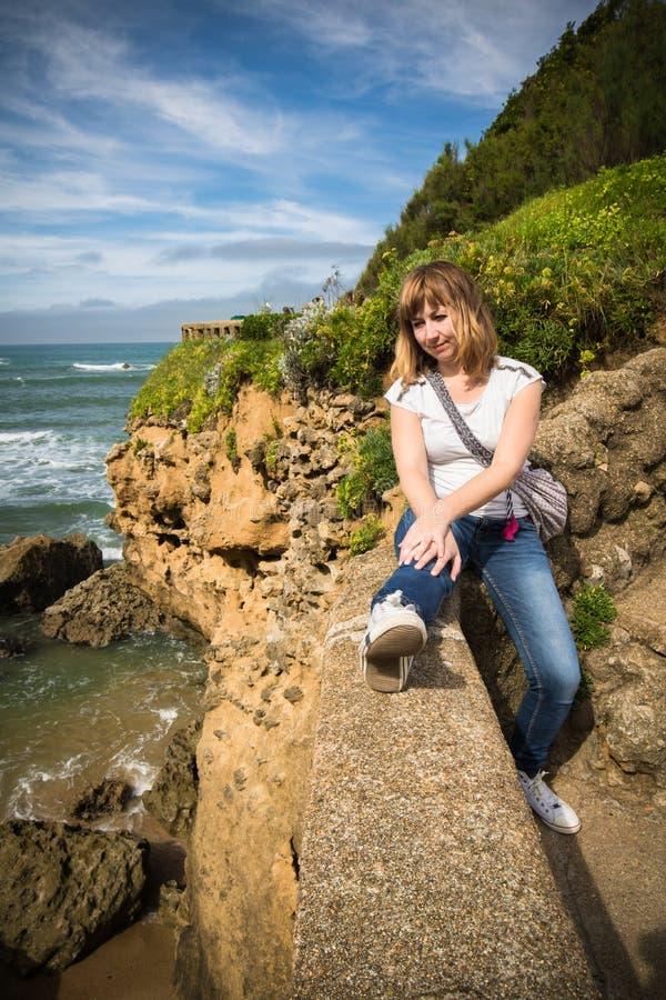 Schöne junge rote behaarte Frau, die wunderbare Zeit auf der atlantischen Küstenlinie sich entspannt im szenischen Meerblick, Bia stockfotos