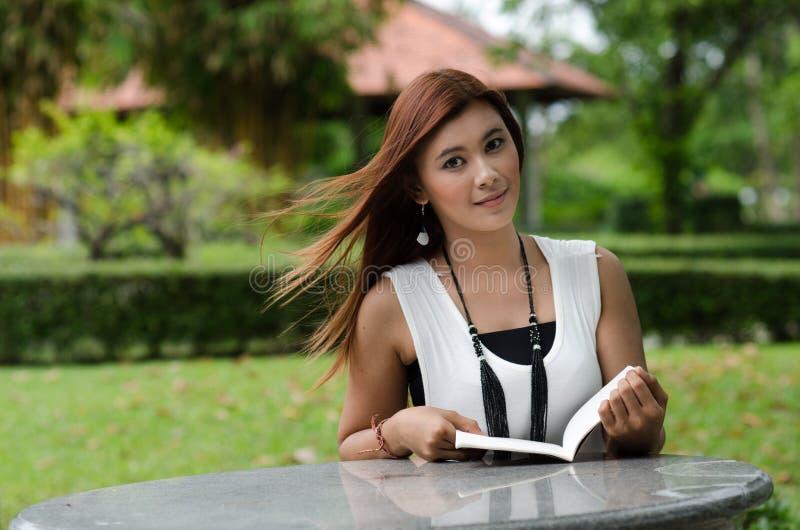 Schöne junge Rothaarigefrau, die draußen liest stockbilder