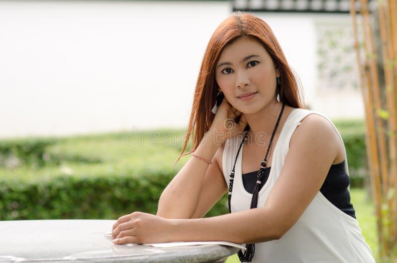 Schöne junge Rothaarigefrau, die draußen liest stockfotos
