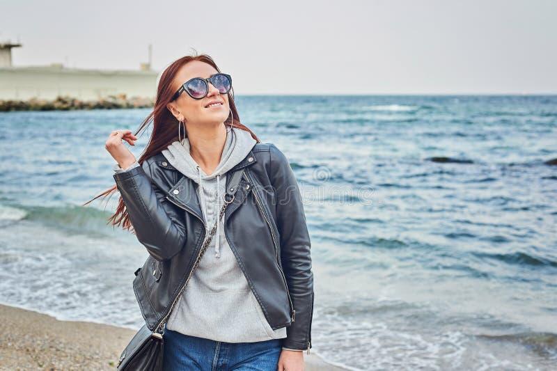 Schöne junge Rothaarigefrau, die am Strand nahe dem Ozean bleibt stockfotos