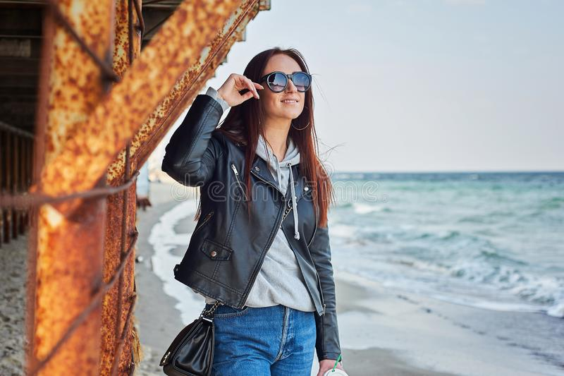Schöne junge Rothaarigefrau, die am Strand nahe dem Ozean bleibt lizenzfreies stockfoto