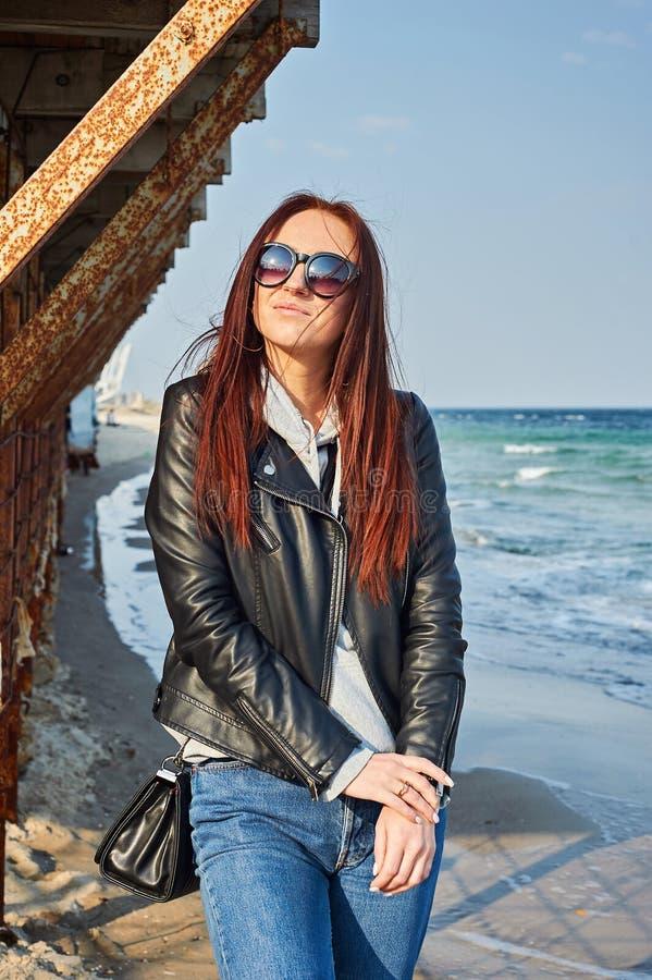 Schöne junge Rothaarigefrau, die am Strand nahe dem Ozean bleibt stockfotografie
