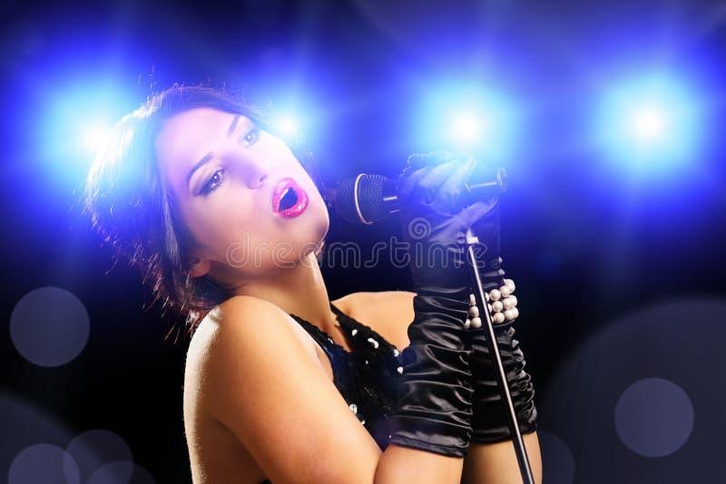 Schöne junge Sängerin im schwarzen Kleid singend lizenzfreie stockbilder