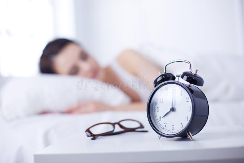 Schöne junge schlafende Frau beim im Bett auf dem Hintergrund des Weckers bequem und himmlisch liegen lizenzfreie stockfotos