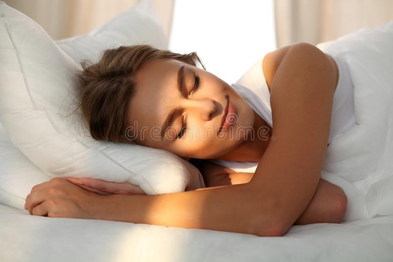 Schöne junge schlafende Frau beim im Bett bequem und himmlisch liegen Sonnenstrahldämmerung auf ihrem Gesicht stockbild