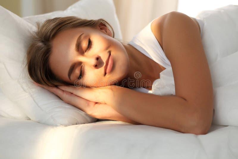 Schöne junge schlafende Frau beim im Bett bequem und himmlisch liegen Sonnenstrahldämmerung auf ihrem Gesicht stockfotos