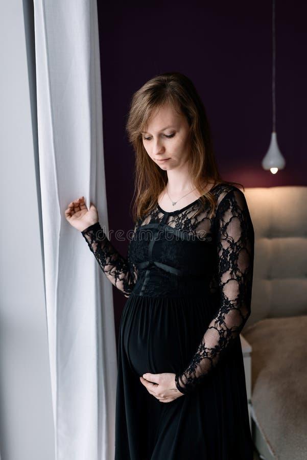 Schöne junge schwangere Frau im Schlafzimmer Tragendes schwarzes Kleid stockfotos