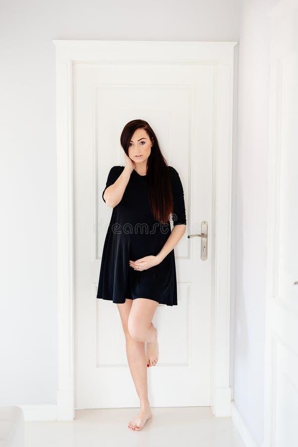 Schöne junge schwangere Frau im schwarzen Kleid lizenzfreies stockfoto