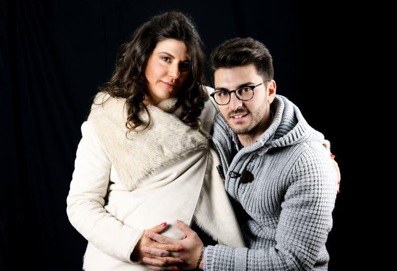Schöne junge schwangere Paare in der Winterkleidung umfasst stockfoto