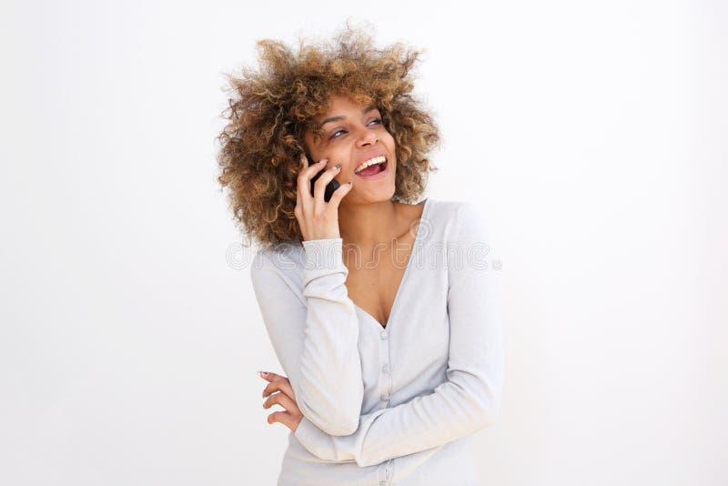 Schöne junge schwarze Frau, die auf Mobiltelefon gegen Whithintergrund spricht stockfotos