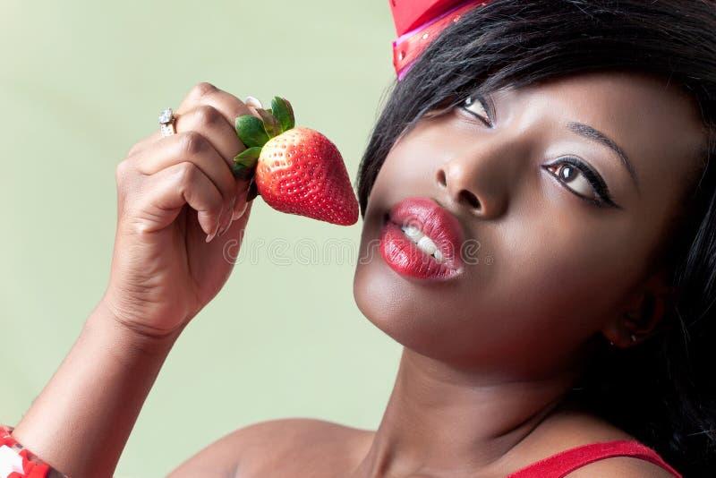 Schöne junge schwarze Frau, die eine Erdbeere isst lizenzfreie stockfotos