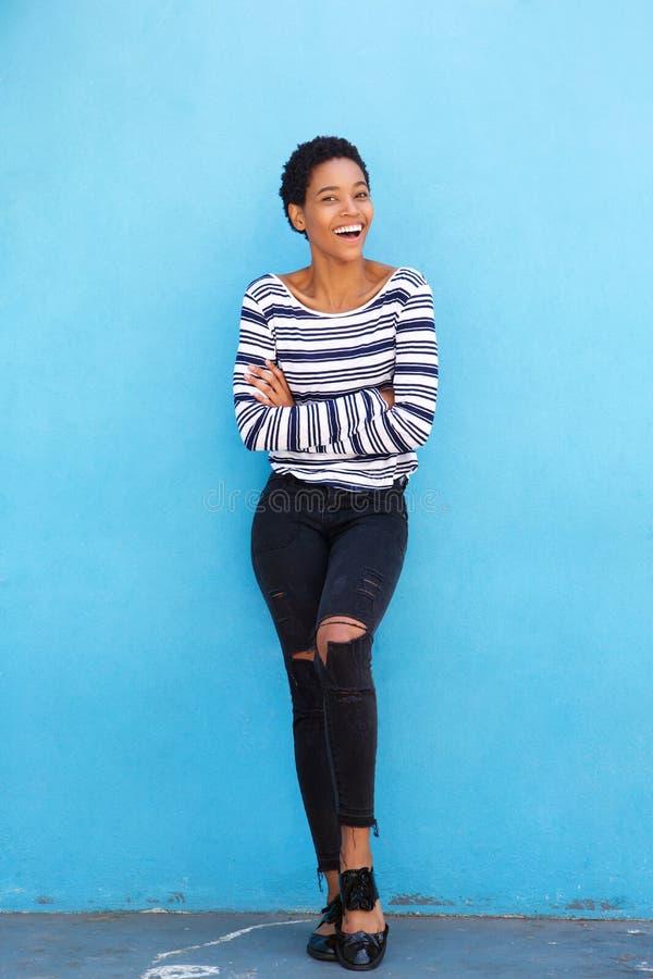 Schöne junge schwarze Frau, die gegen blaue Wand in gestreiftem Hemd lächelt stockfotografie