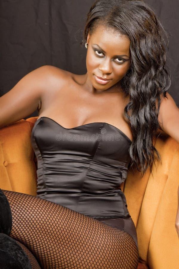 Schöne junge schwarze Frau im Stuhl lizenzfreie stockfotografie