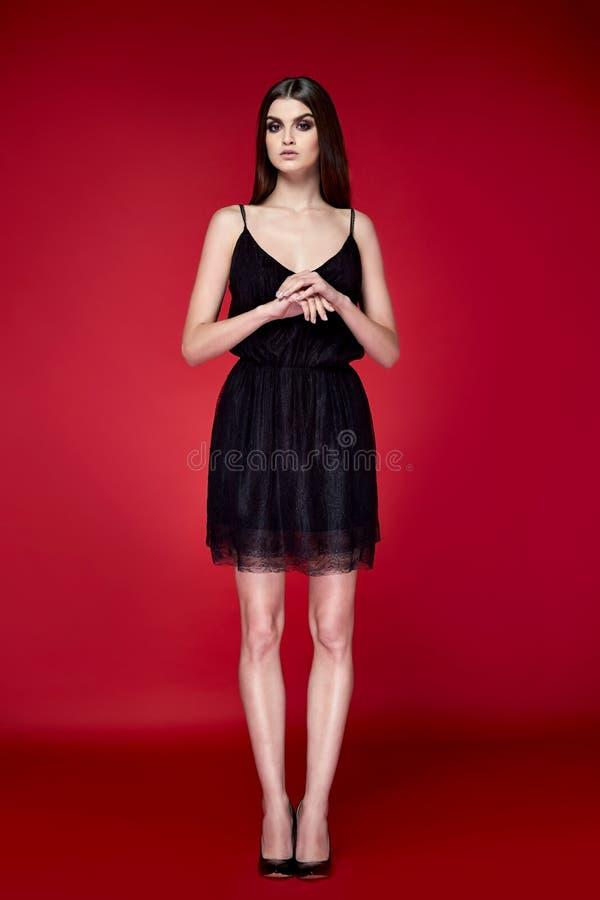 Schöne junge sexy Frau mit dünner Zahl gebräuntes Körpermake-up des langen Sports Haar Brunette perfekten, das ein Smoking-Rock c lizenzfreie stockfotografie
