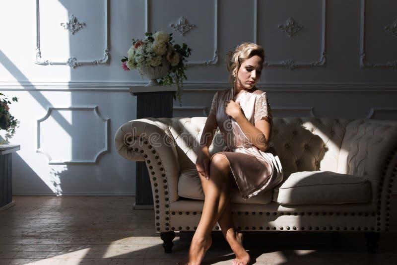 Schöne junge sexy Frauenblondine in einer Seidenrobe sitzt auf dem Sofa gegenüber von dem Fenster in den Strahlen des Vorfalllich stockbild