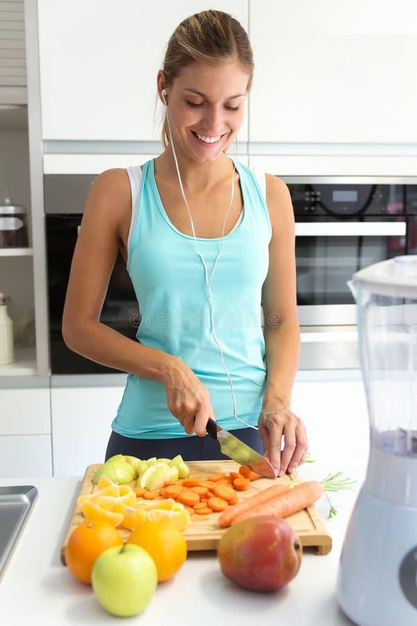 Schöne junge sportliche Frau, die etwas Gemüse und Früchte beim Hören Musik in der Küche schneidet lizenzfreies stockfoto