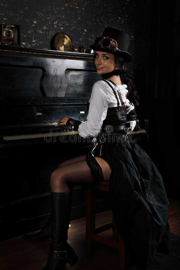 Schöne junge steampunk Frau, die das Klavier spielt lizenzfreie stockfotografie