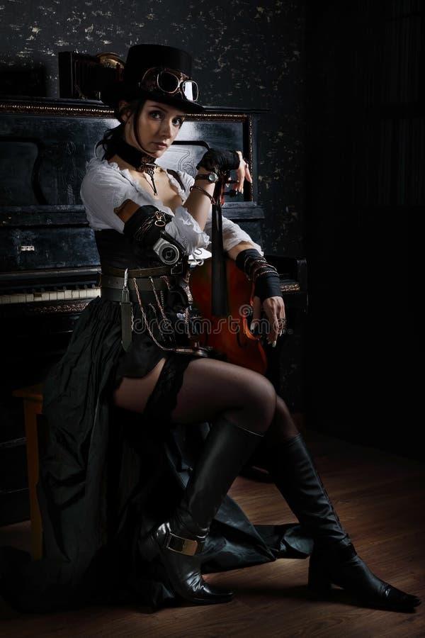 Schöne junge steampunk Frau sitzt an einem Klavier lizenzfreie stockfotos