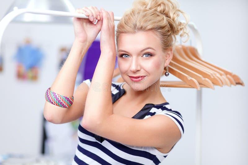 Schöne junge Stilistfrau nahe Gestell mit Aufhängern lizenzfreie stockfotografie