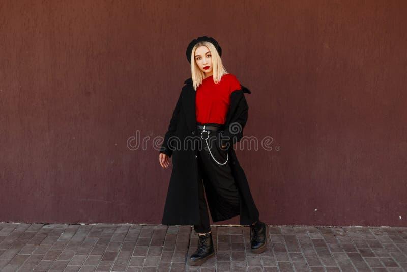 Schöne junge stilvolle Frau in einem modernen schwarzen Mantel mit einem roten Hemd und schwarzen Lederschuhen, die stehen und au stockfotos