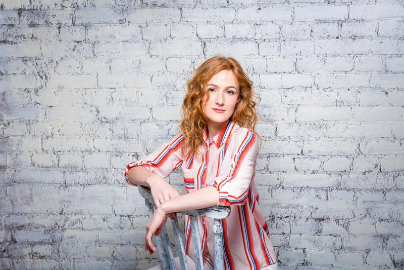 Schöne junge Studentin des Porträts mit dem roten gelockten Haar und den Sommersprossen auf ihrem Gesicht, das zurück auf einem H lizenzfreie stockfotografie