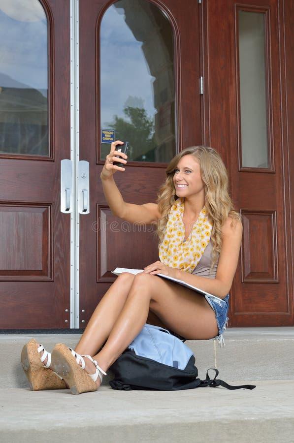 Schöne junge Studentin nimmt ein selfie stockbilder