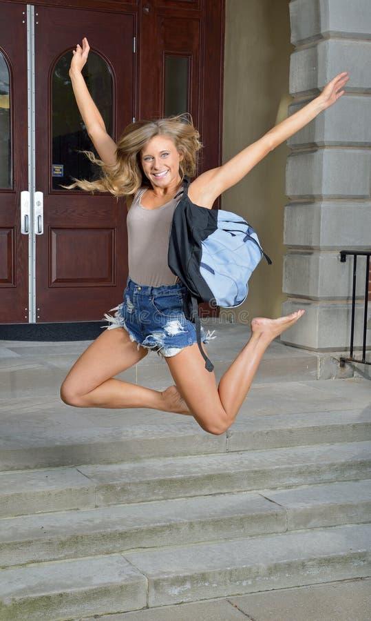 Schöne junge Studentin springt für Freude außerhalb des Gebäudes lizenzfreies stockbild