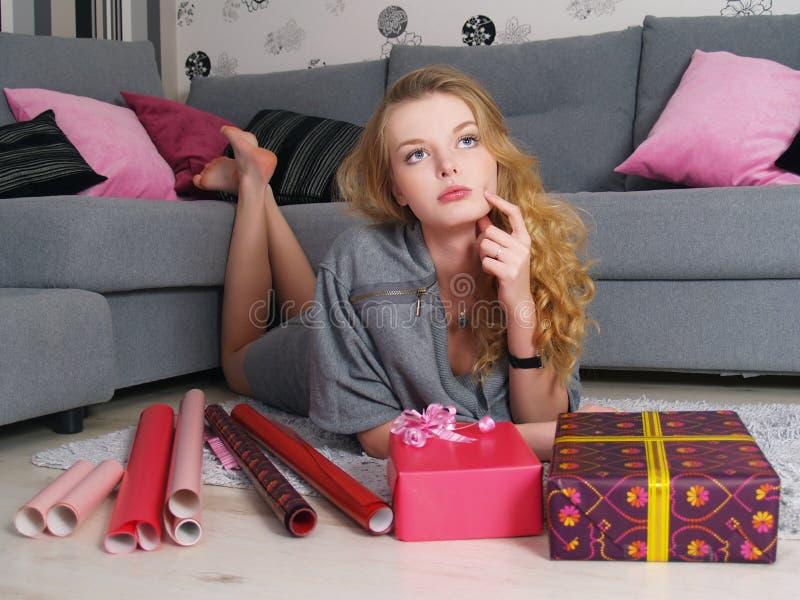 Schöne junge träumende Frau mit Geschenken stockfotos