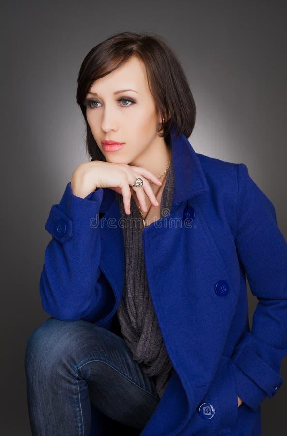 Schöne junge und überzeugte Frau Tragender dunkelblauer Wintermantel stockfotografie