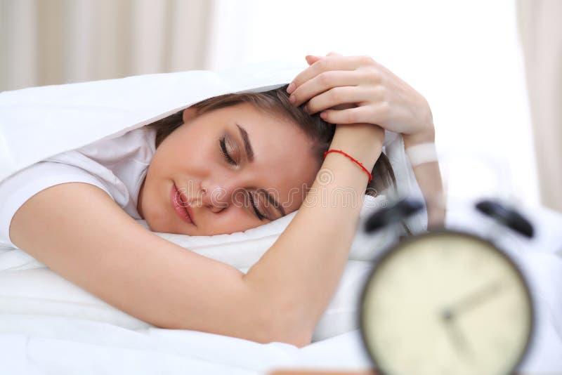 Schöne junge und glückliche schlafende Frau beim im Bett bequem liegen und himmlisch lächeln lizenzfreie stockfotos