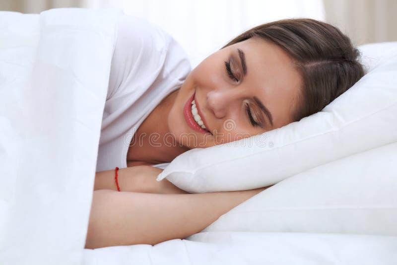 Schöne junge und glückliche schlafende Frau beim im Bett bequem liegen und himmlisch lächeln stockfotos