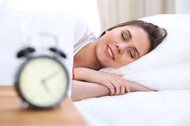 Schöne junge und glückliche schlafende Frau beim im Bett bequem liegen und himmlisch lächeln stockbild