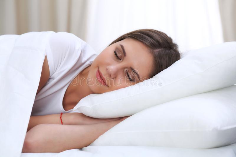 Schöne junge und glückliche schlafende Frau beim im Bett bequem liegen und himmlisch lächeln stockfotografie