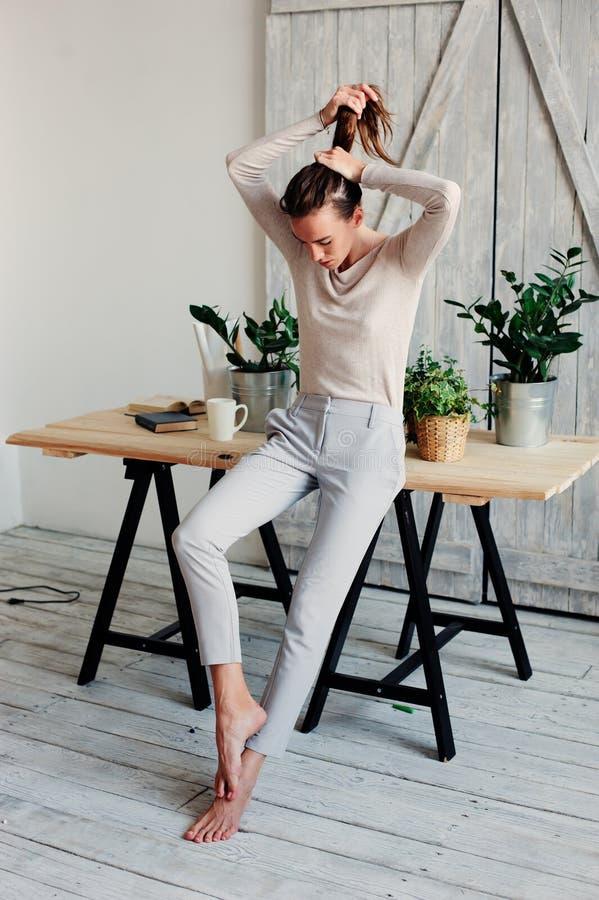schöne junge weibliche Frau, die sich zu Hause am faulen Wochenendenmorgen mit Tasse Kaffee entspannt lizenzfreie stockfotos