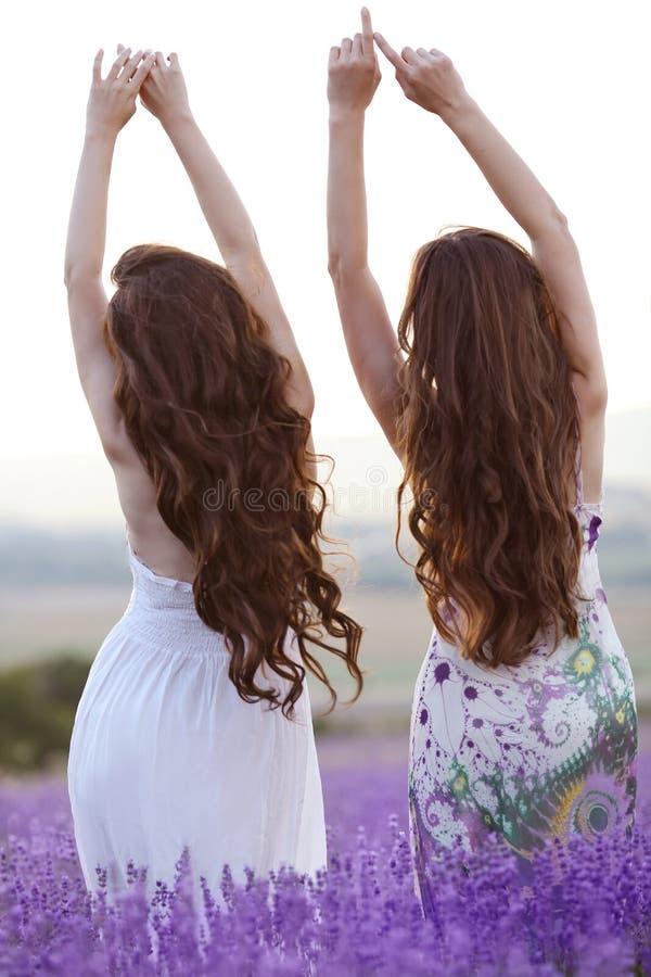 Schöne Junge zwei Frauen über einem violetten Lavendelfeld, in geprüft stockfotos