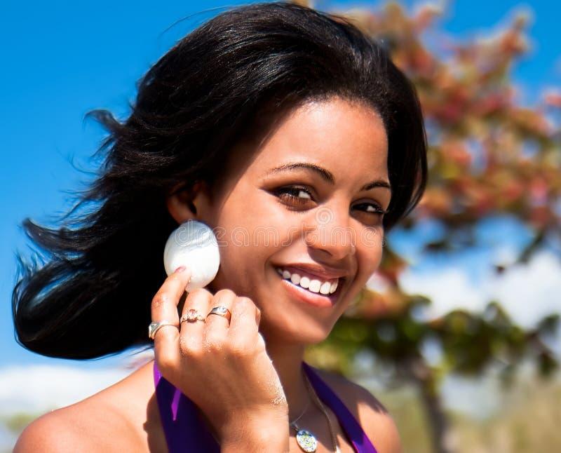 Schöne karibische Frau, die ein Tritonshornshell anhält lizenzfreies stockfoto