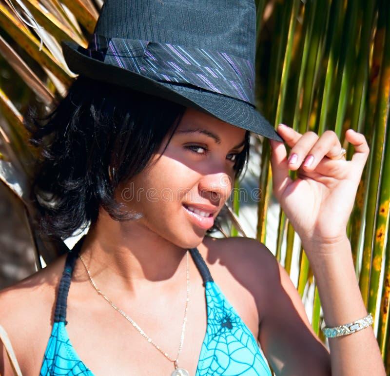 Schöne karibische Frau mit dem schwarzen Hut, der unter der Palme aufwirft stockbild