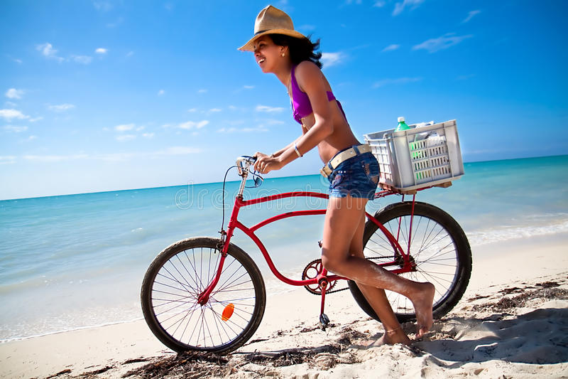 Schöne karibische Frau mit Fahrrad stockfotografie