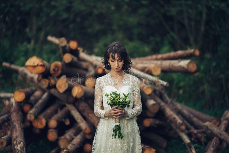 Schöne kaukasische Braut im Hochzeitskleid mit dem Blumenstrauß, der i aufwirft lizenzfreie stockfotos