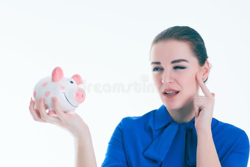 Schöne kaukasische Brunettefrau hört auf den Ton von coinsin ein piggybank und Träume lizenzfreies stockfoto