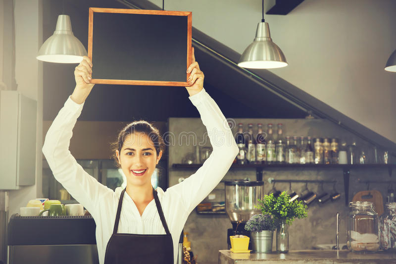 Schöne kaukasische Frau in barista Schutzblech, das leeres Tafelzeichen innerhalb der Kaffeestube hält lizenzfreie stockfotografie