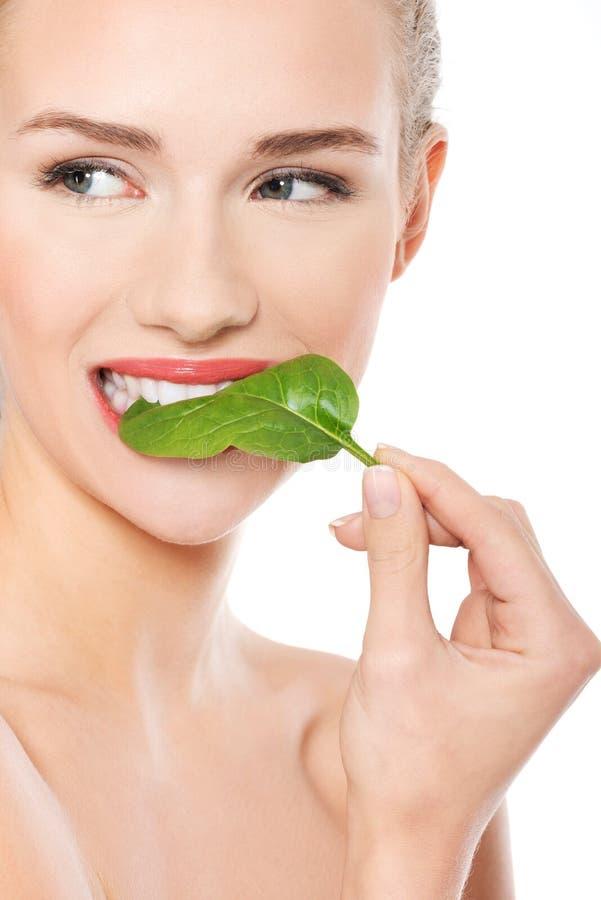 Schöne kaukasische Frau, die frisches grünes Blatt isst. lizenzfreies stockfoto