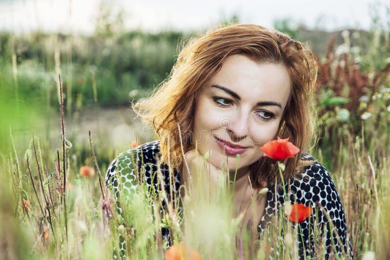 Schöne kaukasische Frau, die mit Mohnblumenblumenfeld, summe aufwirft lizenzfreie stockbilder