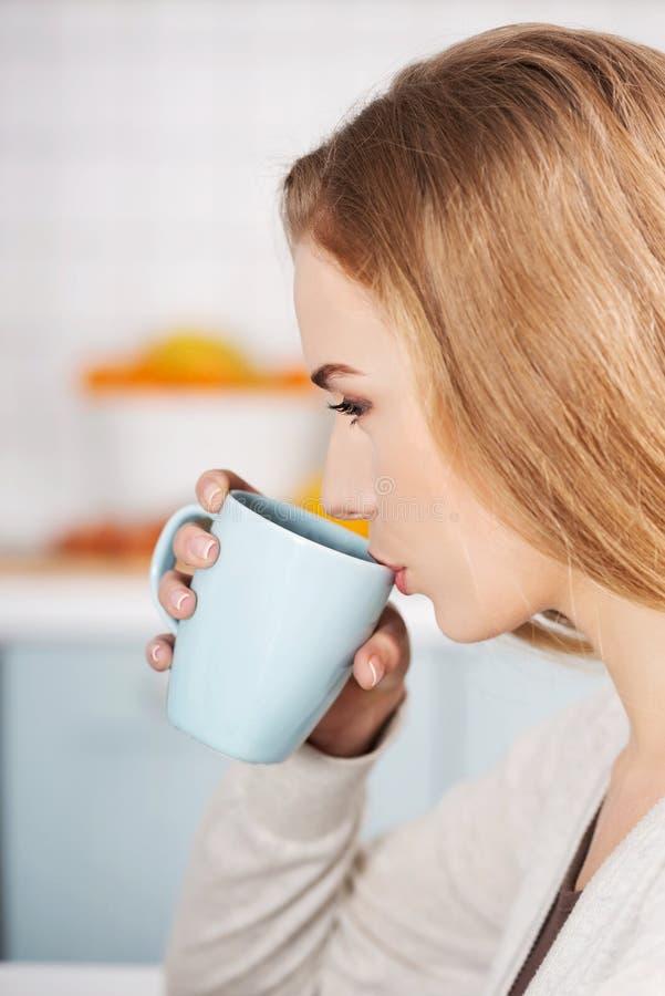 Schöne kaukasische Frau trinkt heißes Getränk, Profil lizenzfreie stockfotos