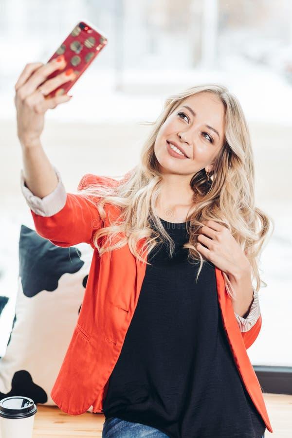 Schöne kaukasische junge Frau im roten Mantel, der selfie Innen gegen Fenster macht stockfotografie