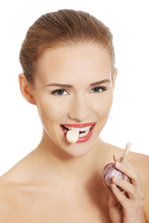 Schöne kaukasische schulterfreie Frau mit rohem Knoblauch im Mund. stockbild