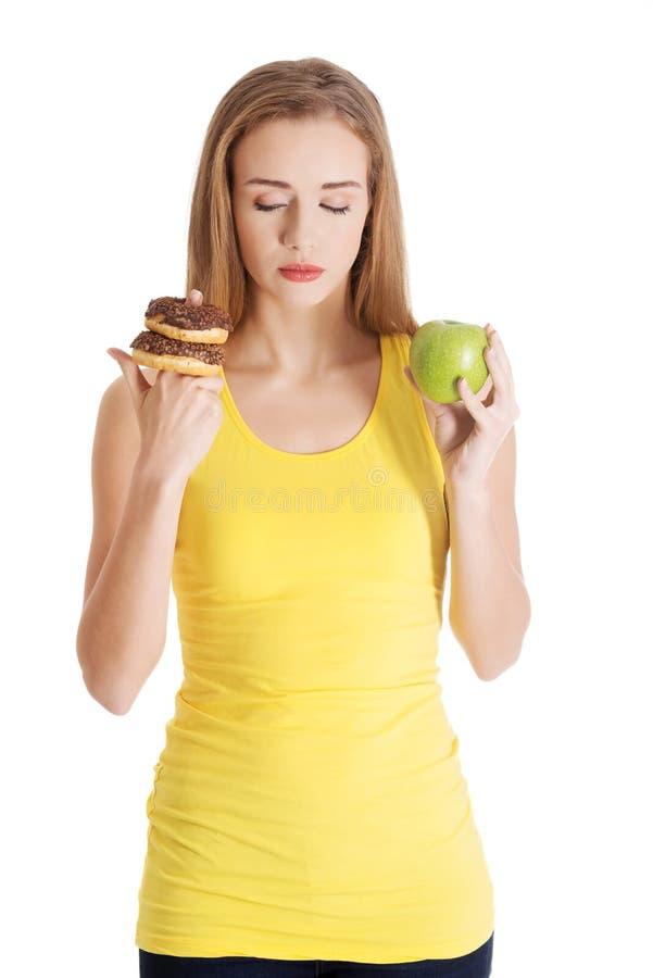 Schöne kaukasische zufällige Frau mit Donuts und Apfel. stockfoto